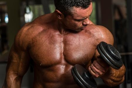 haciendo ejercicio: culturista haciendo ejercicios de peso pesado para bíceps con mancuernas