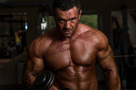 hombres haciendo ejercicio: culturista haciendo ejercicios de peso pesado para bíceps con mancuernas