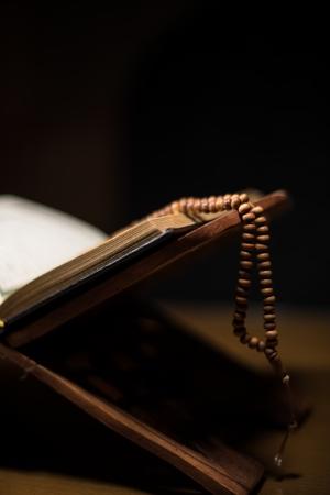 Seiten von Koran und Rosenkranz auf das Buch
