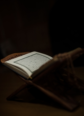 pages of holy koran and rosary at the book