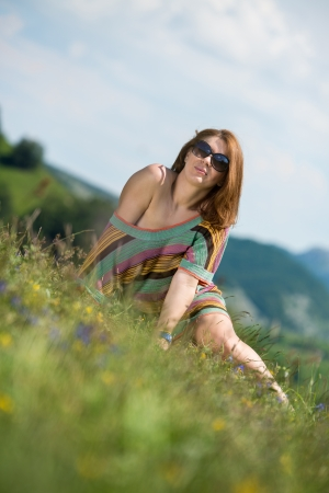 beautiful woman in dress sitting on the grass photo