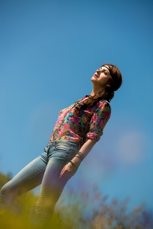 beautiful woman in jeans standing on the grass photo