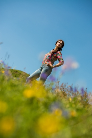 aciculum: beautiful woman in jeans standing on the grass