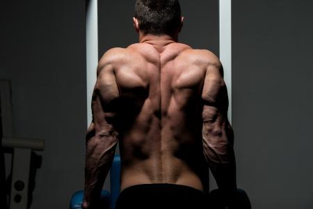 culturista: joven culturista masculino haciendo ejercicios de peso pesado