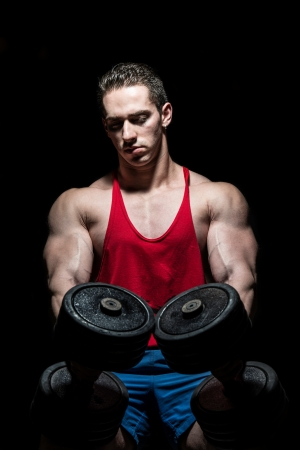 young bodybuilder posing with dumbbell at the bench on black background photo