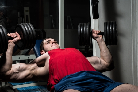 young bodybuilder doing bench press for chest photo
