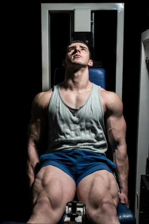 bodybuilder doing heavy weight exercise for legs on machine leg extensions Stock Photo
