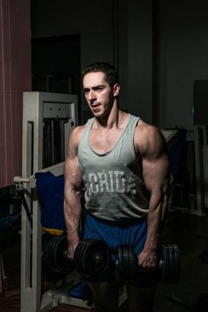 bodybuilder doing heavy weight exercise for shoulder white dumbbell Stock Photo - 21051489