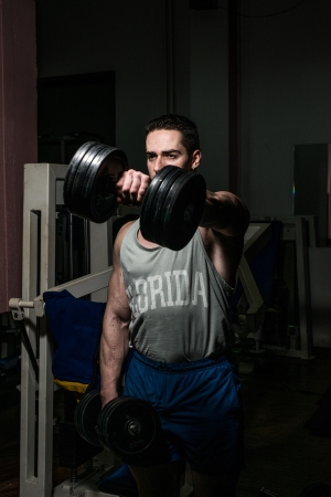 bodybuilder doing heavy weight exercise for shoulder white dumbbell Stock Photo - 21051490