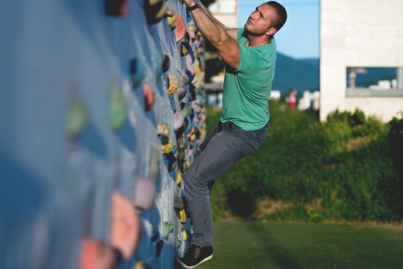 clambering: young man climbing wall rock outdoors Stock Photo