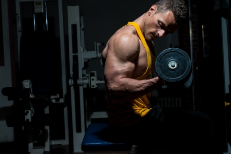 young man doing heavy weight exercise for biceps Stock Photo - 21063954