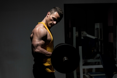 heavy lifting: young man doing heavy weight exercise for biceps