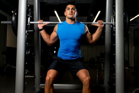 healthy body: Fitness Trainer doing squats with barbells Stock Photo