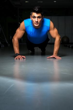 Man exercising in gym push ups Stock Photo