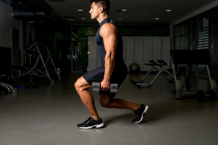 lunges: Young Man Exercising Lunges with Weights