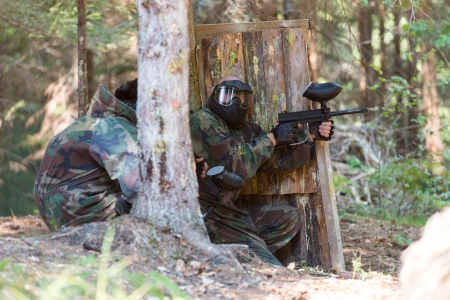Paintball Players Hide Behind Tree photo