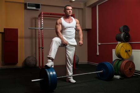 Bodybuilder preparing for deadlift of barbell photo