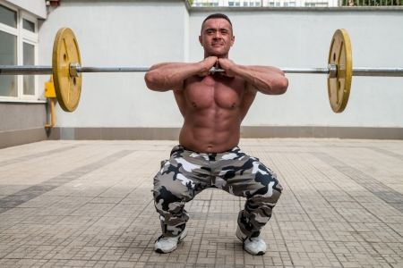 Bodybuilder Doing Front Squats With Barbells photo