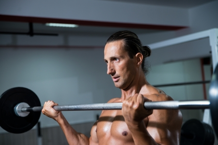 Man In The Gym Exercising Biceps With Barbell photo