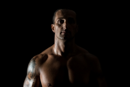 Muscular man in a black background photo