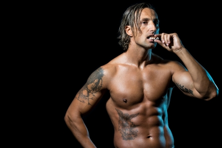 Bodybuilder Eating Chocolate Stock Photo - 22602731