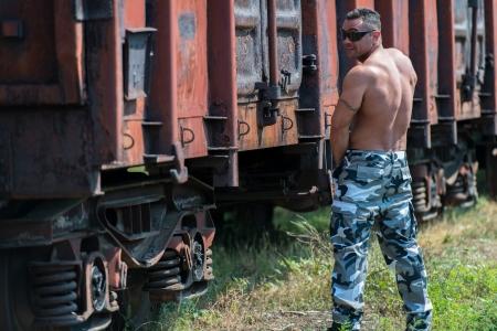 pissing: Muscular Man Pissing On Railroad