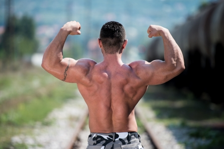Man Showing His Back Double Biceps photo