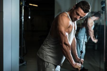 Bodybuilder tun Heavy Weight Übung für Trizeps mit Kabel