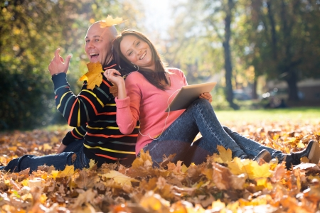 Couple With Headphones Enjoying Music In Autumn photo