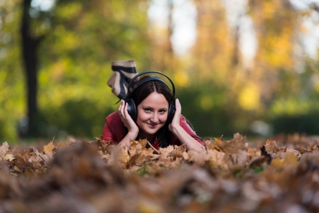 Young Girl With Headphones Enjoying Music In Autumn photo