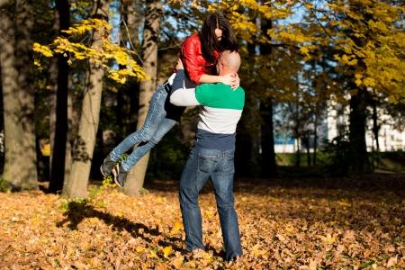 Man Carrying Woman Ride Through Autumn Woods photo