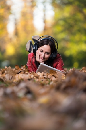 Girl Listening To Music On Autumn Leaves