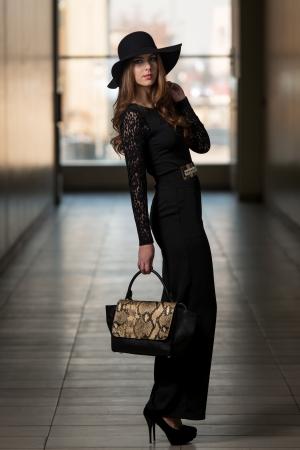 Elegante Dame mit stilvollen Hut und Ledertasche