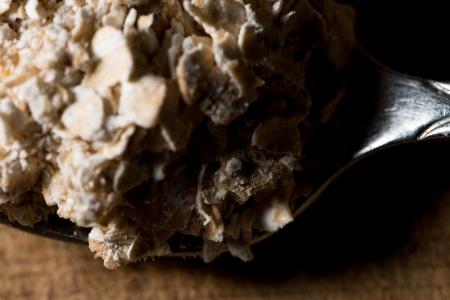 avena en hojuelas: Copos de avena en la cuchara de metal Foto de archivo