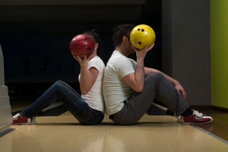Young Couple Hiding Their Faces Behind Bowling Ball photo