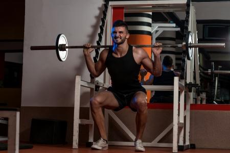 squats: Men Doing Squats Stock Photo