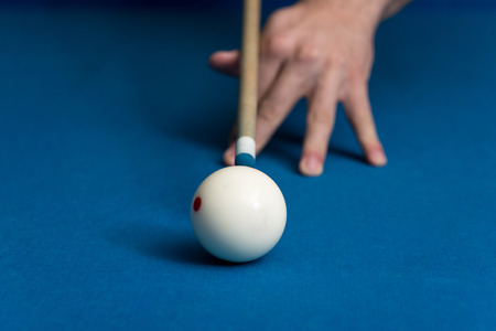pool hall: Man Playing Pool About to Hit Ball