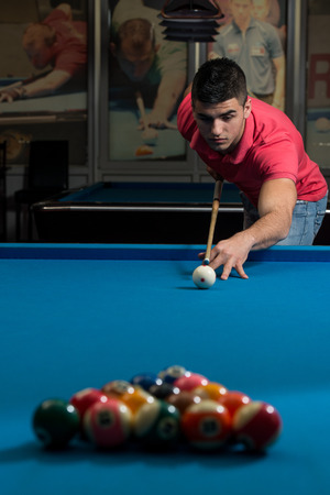 pool hall: Young Man Lines Up A Shot