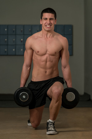 Young Man Exercising Lunges with Weights