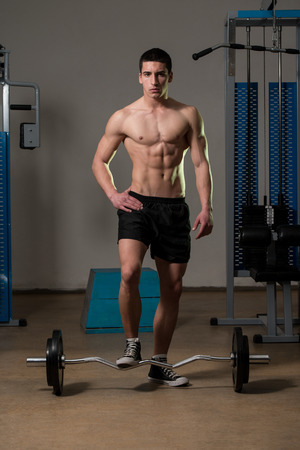 men standing: Young Muscular Men Standing By The Barbell
