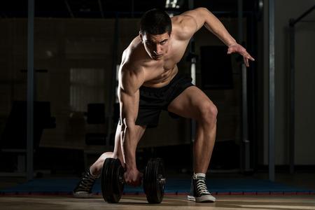 Junge Bodybuilder Heben schwerer Hantel