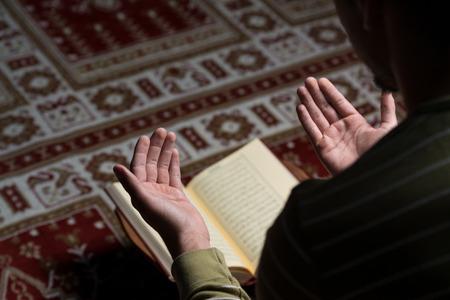 イスラム教徒の男性がコーランを読んでください。 写真素材