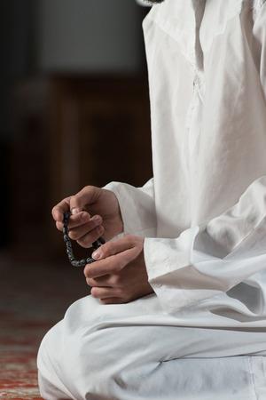 dishdasha: Young Muslim Man Making Traditional Prayer To God While Wearing A Traditional Cap Dishdasha Stock Photo