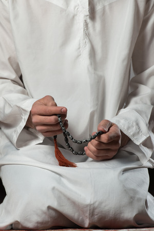 muslim prayer: Young Muslim Man Making Traditional Prayer To God While Wearing A Traditional Cap Dishdasha Stock Photo
