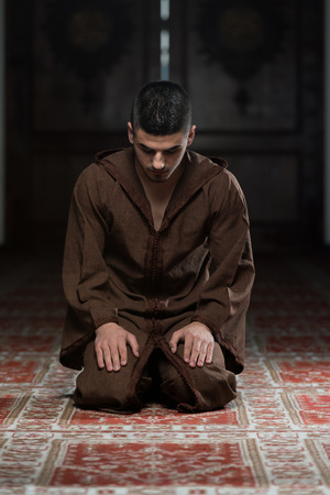 muslim prayer: Young Muslim Man Making Traditional Prayer To God While Wearing A Traditional Cap Djellaba