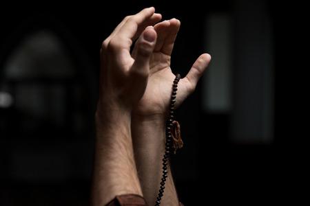 manos orando: Manos sosteniendo un rosario musulmán en la mezquita