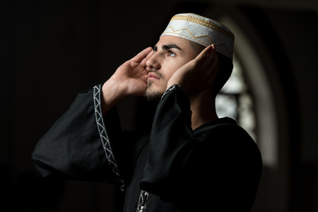 dishdasha: Young Muslim Guy Making Traditional Prayer To God While Wearing A Traditional Cap Dishdasha