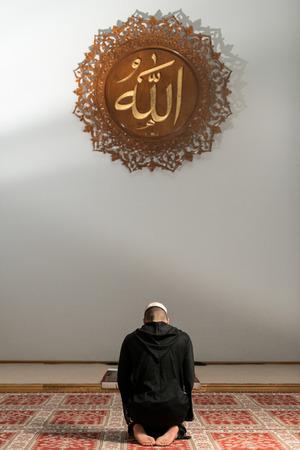 Junge muslimische Kerl, der traditionelle Gebet zu Gott, während trägt einen traditionellen Kappe Dishdasha