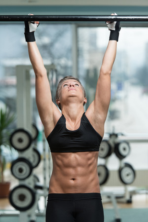 raises: Fitness Woman Performing Hanging Leg Raises Exercise - One Of The Most Effective Ab Exercises Stock Photo