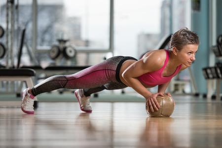 Attractive Female Athlete Darstellende Liegestütze auf Medizinball Standard-Bild